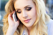 Beautiful blonde girl talking by phone
