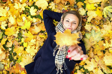 Young woman dreaming in autumn leaves