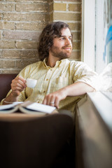 Man With Coffee Cup Looking Through Window In Cafe