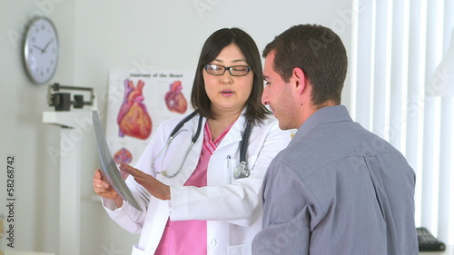 Japanese doctor reviewing x-ray with male patient