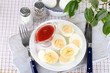 Boiled eggs on plate on wooden board on tablecloth
