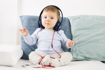 Sweet baby boy listening music at headphones in conducting posit