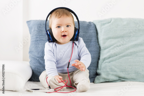 Cute baby boy listening music at headphones.