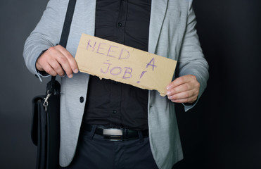 """Businessman holding sign """"need a job"""""""