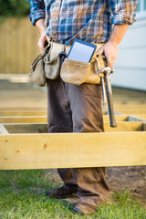 Carpenter With Tablet Computer And Hammer In Tool Belt