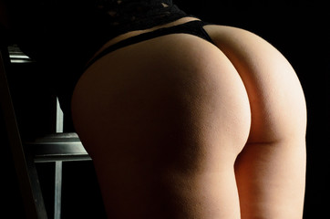 Female buttocks in black underwear on black background