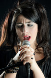 Woman singing with microphone on black background