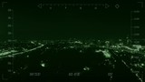 Military drone flying over city at night