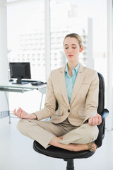 Lovely classy businesswoman meditating in lotus position on her