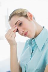 Exhausted chic businesswoman having headache sitting on her swiv