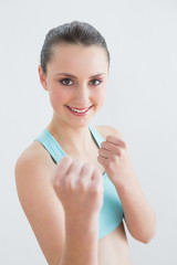 Smiling fit woman clenching fists against wall