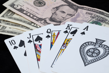 Royal Flush and bank note on black background