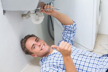 Plumber repairing washbasin drain while gesturing thumbs up