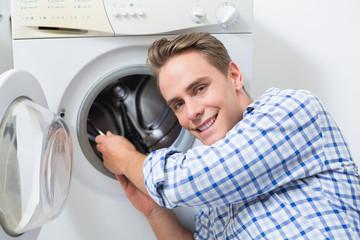 Smiling technician repairing a washing machine