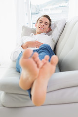 Full length of a relaxed young man lying on sofa
