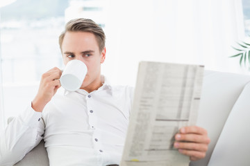Relaxed man drinking coffee while reading newspaper on sofa