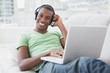 Smiling young Afro man with headphones using laptop on sofa