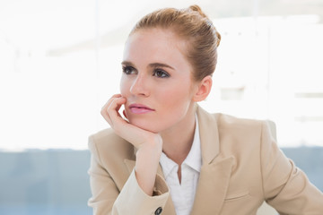 Thoughtful businesswoman in bright office