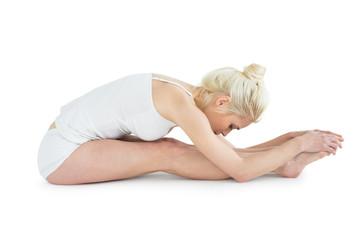 Toned young woman doing the paschimottanasana pose