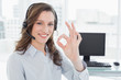 Businesswoman wearing headset while gesturing ok sign in office