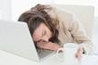 Businesswoman resting head on laptop keyboard