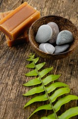 Bowl of stones ans soap with green fern on old wood