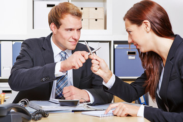 Two business people fighting with pens
