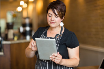 Female Owner Using Digital Tablet In Cafe