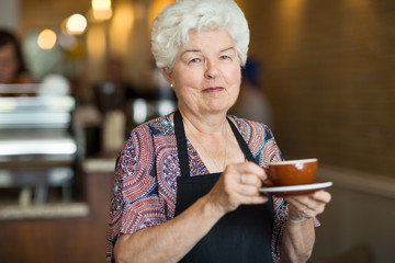 Waitress Holding Coffee Cup And Saucer In Cafe