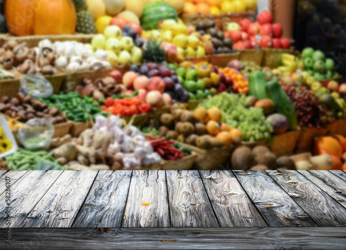 Background with empty wooden table and blured fruits and vegetab