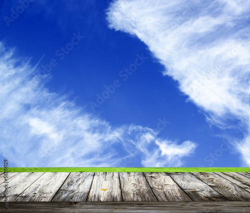 Background with empty wooden table over beautiful meadow