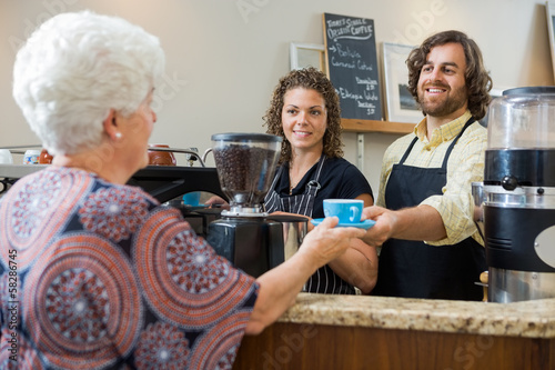 Waitress With Colleague Serving Coffee To Woman At Counter