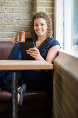 Woman With Digital Tablet And Coffee Mug In Cafeteria
