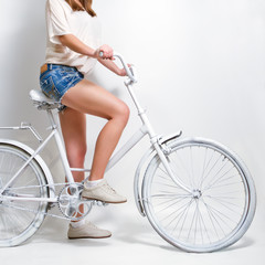 Young woman riding a white vintage bicycle
