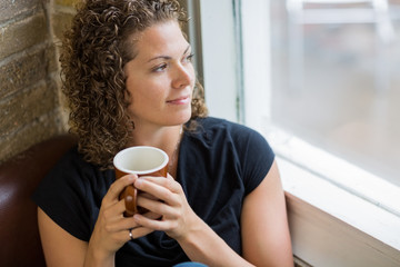 Thoughtful Woman With Coffee Mug In Cafe