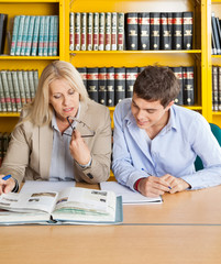 Teacher And Student Looking At Book While Sitting In Library