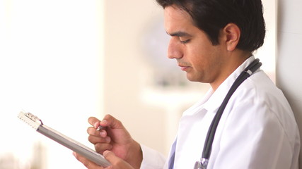 Hispanic doctor working on medical chart