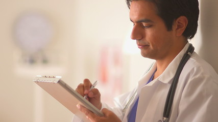 Mexican doctor filling out medical chart