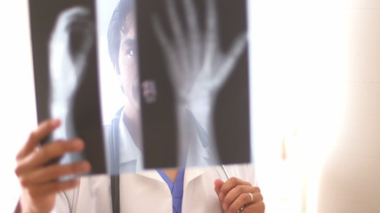Hispanic doctor reviewing hand x-rays