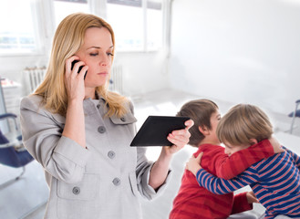 busy mother with tablet and mobile while her children fighting