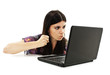 The young woman threatens with a fist to the laptop