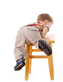 Little boy climbing on stool