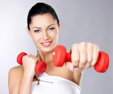Photo of a healthy training young woman with dumbbells