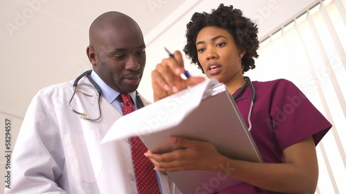 African American medical professionals reviewing medical charts