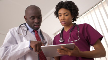 African American doctors reviewing medical charts