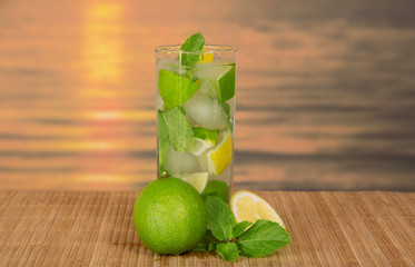 Glass with mojito, juicy lime and spearmint leaf