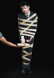 Businessman tied up with adhesive tape and looking to toast with greed poster