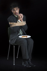Businessman tied up with adhesive tape and looking to toast on a plate