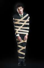 Businessman tied up with adhesive tape and looking sad