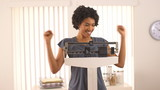 Black woman excited about weight loss on scale